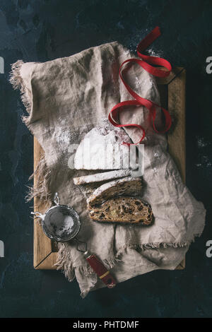 Sliced Christmas cake, traditional German festive baking. Wholegrain stollen with raisins and sugar powder on linen napkin, wooden tray, sieve, red ri - Stock Photo
