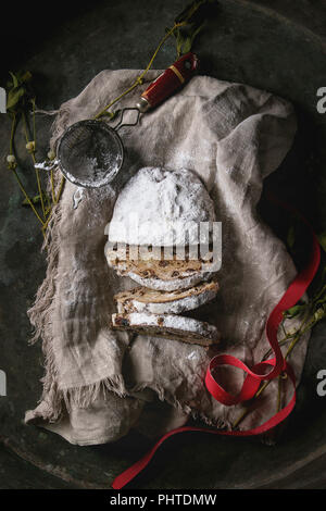 Sliced Christmas cake, traditional German festive baking. Wholegrain stollen with raisins and sugar powder on linen napkin with sieve, red ribbon, mis - Stock Photo