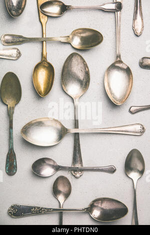 Collection of old vintage spoons on grey background. - Stock Photo