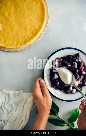 A woman sprinkling sugar over pitted cherries in a white bowl on grey background photographed from top view. Green leaves, white linen and pie dough a - Stock Photo