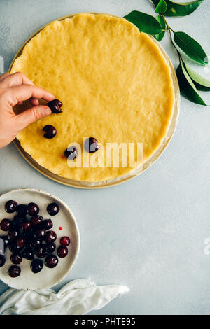A woman placing pitted cherries on a pie dough and pitted cherries on a white plate on the side photographed from top view. Green leaves accompany. - Stock Photo
