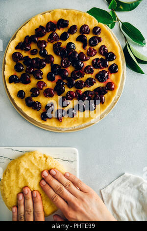 A woman rolling out a pie dough on a white marble cutting board photographed from top view. A pie dough topped with cherries and green leaves accompan - Stock Photo