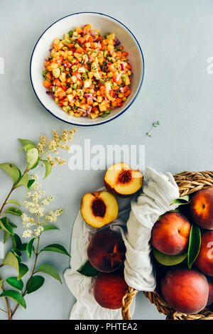 Peach salsa in a white bowl accompanied by a basket of fresh peaches and tiny flowers photographed on a grey background from top view. - Stock Photo