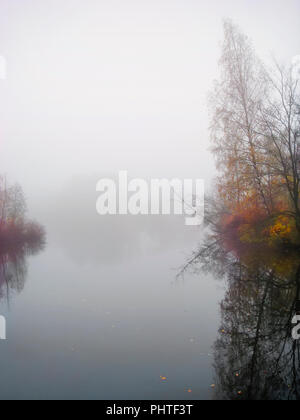 Foggy dawn, autumn forest in mystic fog in the morning, lake at dawn with clouds reflected in the calm water, thick dense fog. - Stock Photo