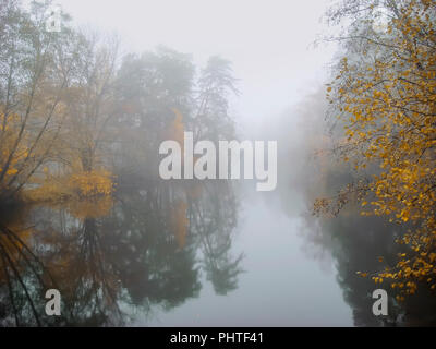 Foggy dawn. Colorful autumn forest near the lake, mistic fog in the morning, lake at dawn with clouds reflected in the calm water, thick dense fog - Stock Photo