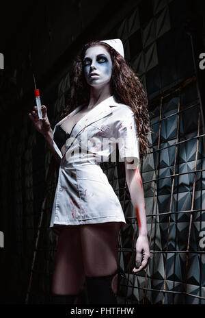 Horror shot: the creepy wicked insane nurse (doctor) in bloody uniform, with syringe in hand. Zombie woman (living dead) - Stock Photo
