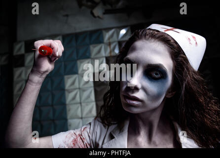 Horror shot: the scary evil insane nurse (doctor) attacking by bloody syringe. Zombie woman (living dead). Monster from nightmare - Stock Photo