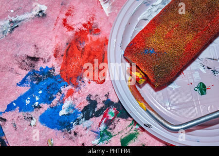 Colorful roller lying on the white plate after beign used by a professional artist for wall art painting close-up, colorful pink background - Stock Photo