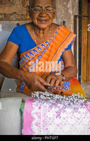 Vertical portrait of an old lady making bobbin lace in Sri lanka. - Stock Photo
