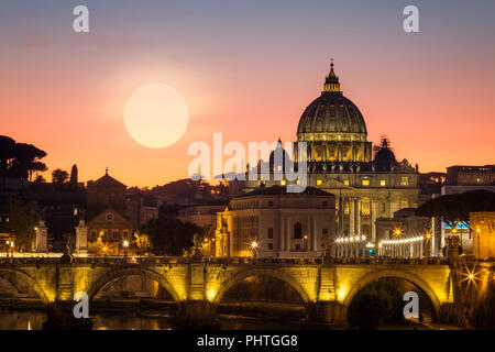 The sun sets behind Vatican City in Rome, Italy. - Stock Photo