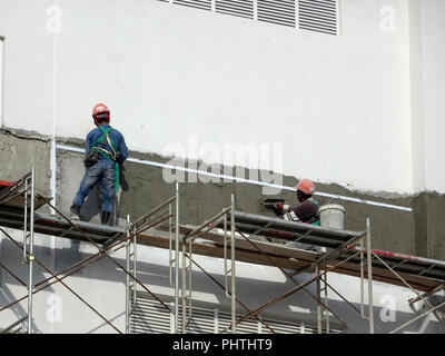 Construction workers plastering wall using cement plaster at the construction site. They are wearing appropriate safety gear to prevent bad happen - Stock Photo