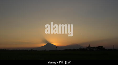 Sunset light between Mount Merapi (left) and Mount Merbabu (right), Central Java, Indonesia - Stock Photo