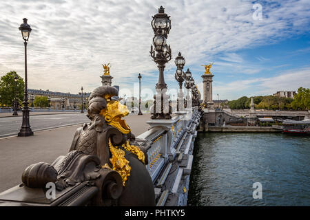 View across the Alexandre III Bridge with gilded statues and rows or ornate lamp in Paris, France on 26 August 2018 - Stock Photo