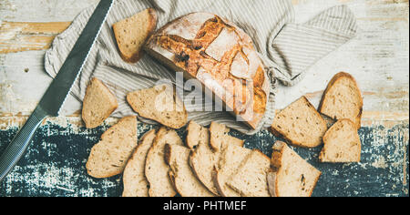 Sourdough wheat bread cut in slices on table, wide composition - Stock Photo