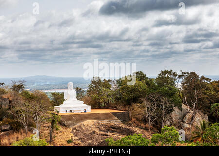 The great statue of the Buddha at the sacred mountain of Mihintale in Sri Lanka - Stock Photo