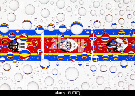 Flags  of Swaziland behind a glass covered with raindrops. 3D illustration - Stock Photo