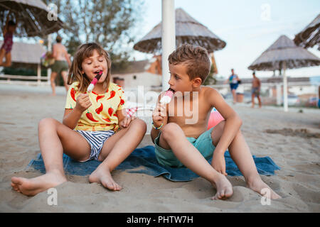 Happy positive children sitting on the sandy beach and eating ice cream. People, children, friends and friendship concept - Stock Photo