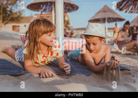 Happy positive children lie on the towel on the beach and playing with sand - Stock Photo