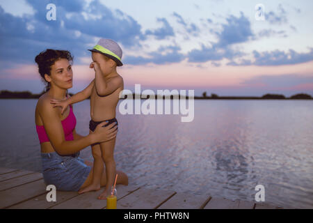 Happy mother with her son enjoy the beautiful sunset while sitting on a wooden pier by the river. Positive human emotions, feelings, joy. Happy family - Stock Photo