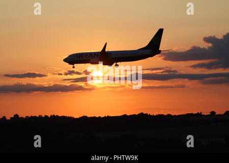 A ryanair boeing 737 jet EI-ESW flies in front of the setting sun as it makes its final approach into Edinburgh airport - Stock Photo
