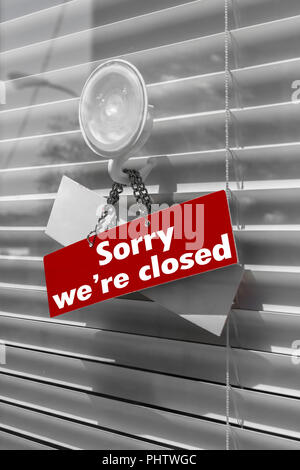 Sign saying sorry we're closed on a glass door - Stock Photo