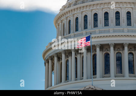 The American flag flying in front of the US Capitol building. - Stock Photo