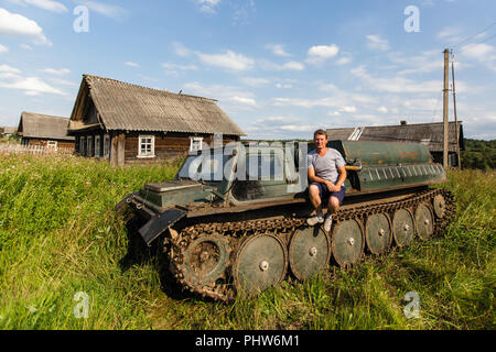 A man sits on the armor of old all-terrain vehicle in the Russian village. - Stock Photo