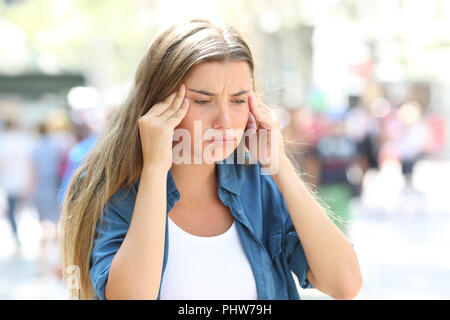 Stressed girl complaining suffering head ache in the street - Stock Photo