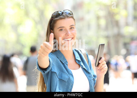 Happy woman smiling holding a smart phone with thumb up in the street - Stock Photo