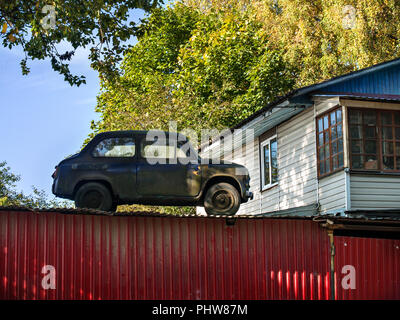 An old retro car stands on the roof of a barn behind a red fence near a white house with large windows on a sunny, clear autumn day close up - Stock Photo