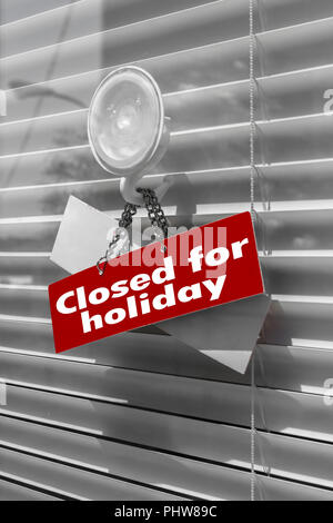 Sign saying Closed for holiday on a glass door - Stock Photo