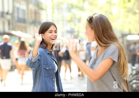 Two happy friends meeting and greeting in the street - Stock Photo