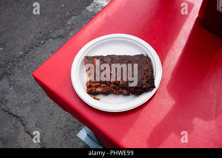 A paper plate of a half-rack barbecue ribs on a red picnic table at The Great New York State Fair. - Stock Photo