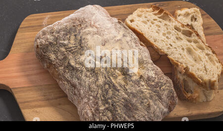 Bread and slices on wooden bread board - Selective focus on rustic bread close up - Stock Photo