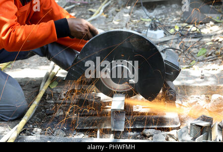 Industry worker cutting metal with grinder. Lots of glowing sparks. - Stock Photo