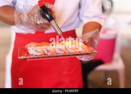 Japanese restaurant chef grilling salmon sushi  - Stock Photo