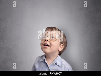Adorable little boy portrait with empty grey wall background - Stock Photo