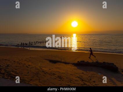 Man running on the beach at sunset, Benguela Province, Benguela, Angola - Stock Photo