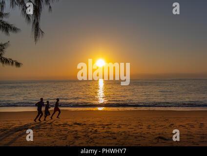 Men running on the beach at sunset, Benguela Province, Benguela, Angola - Stock Photo