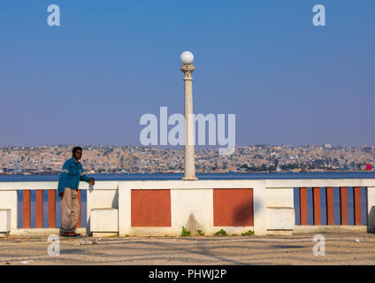 Angolan man leaning on fence, Benguela Province, Lobito, Angola - Stock Photo