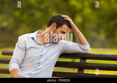 Depressed businessman is sitting at the park and thinking about something.one man - Stock Photo