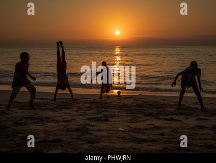 Boys dancing capoeira on the beach at sunset, Benguela Province, Benguela, Angola - Stock Photo