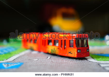 Front of a Siku toy public transport tram on a road mat in soft focus - Stock Photo