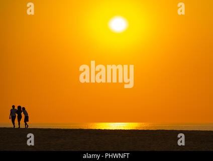 Silhouettes of women at sunset on a beach, Benguela Province, Lobito, Angola - Stock Photo