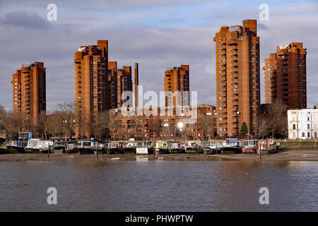High rise World's End estate in Kensington and Chelsea, in bold red brick, seen with houseboats moored on the foreshore of the River Thames - Stock Photo