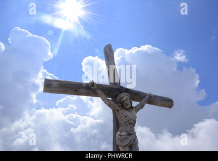 Jesus Christ in front of a blue and cloudy sky - Stock Photo