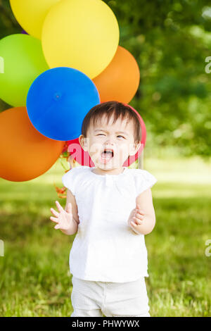 Portrait of cute adorable asian girl child one year old in white shirt with balloons on field meadow park outside, screaning in fear stress, concept o - Stock Photo