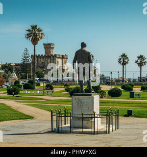 Estoril, Portugal - August 30, 2018: Statue of Fausto Cardoso and Baronial Estoril Castle in background overlooking the ocean - Stock Photo