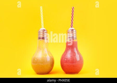 Two lamp- shaped jars with fruit smoothies isolated on yellow background. - Stock Photo