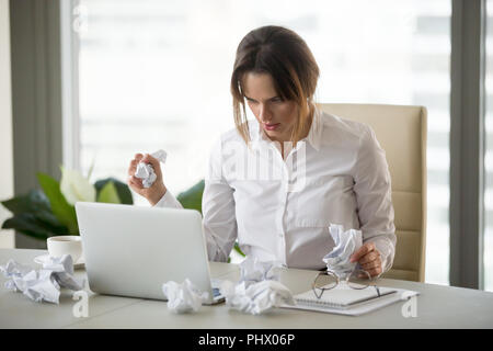 Stressed businesswoman holding crumpled paper trying to finish u - Stock Photo